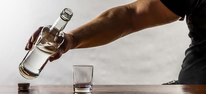 Mann, der nach Schnapsflasche greift und sich ein Glas einfüllt.