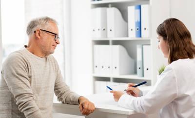 Ärztin, die mit einem älteren Patienten im Gespräch ist.