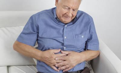 Älterer Mann, der sich mit schmerzverzerrten Gesicht den Bauch hält.