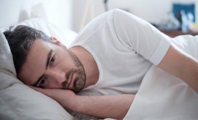 Mann, der erschöpft im Bett liegt.