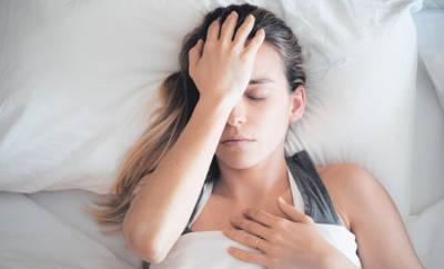 Blasse Frau, die erschöpft im Bett liegt.