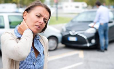 Frau, die sich mit schmerzverzerrten Gesicht den Nacken hält, im Hintergrund zwei Autos, die zusammen gestoßen sind.