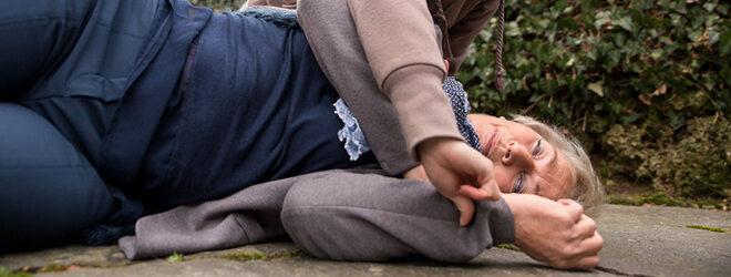 Frau die am Boden liegt, deren Puls gemessen wird.