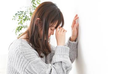 Junge Frau, die sich erschöpft an die Wand lehnt.