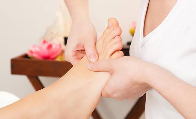 Frau, deren Fuß massiert wird.