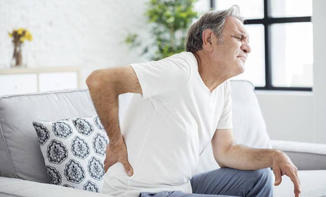 Älterer Mann, der sich mit schmerzverzerrten Gesicht an den Rücken langt.