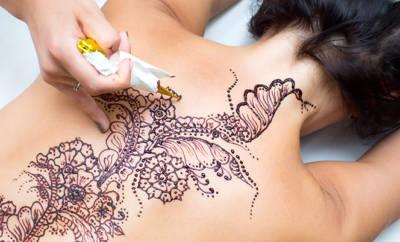 Frau, auf deren Rücken ein Henna Tattoo aufgetragen wird.