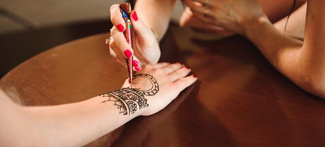 Frau, auf deren Hand ein Henna Tattoo aufgebracht wird.