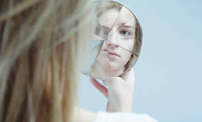 Junge Frau, die verstört in einen zerbrochenen Spiegel blickt.