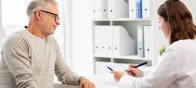 Älterer Mann, der einer jungen Ärztin gegenüber hockt und mit ihr spricht.