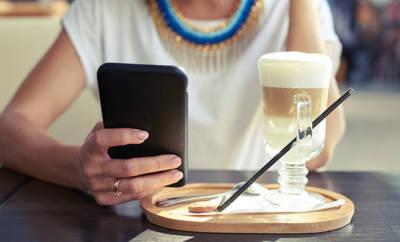 Frau, die Handy in der Hand hält. Kaffee steht daneben.