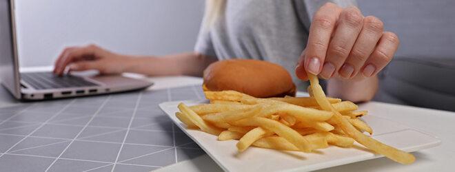 Junge Geschäftsfrau, die am Laptop arbeitet und nebenbei nach einem Burger greift.