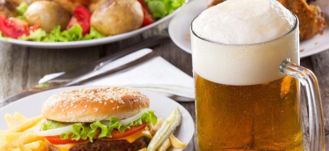 Glas Bier, das neben einem Burger auf dem Tisch steht.