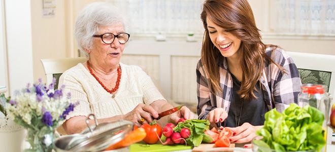 Ältere Frau, die mit Enkelin Gemüse schneidet.