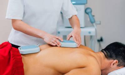 Magnetfeldtherapie am Rücken eines Mannes.