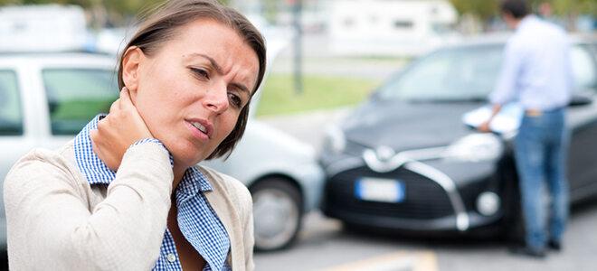 Frau, die sich an den Kopf langt, im Hintergrund Autounfall.