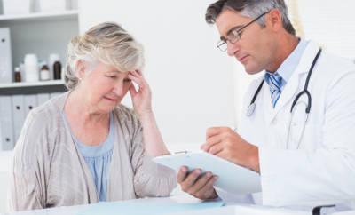 Seniorin die mit Arzt in Gespräch ist und besorgt schaut.