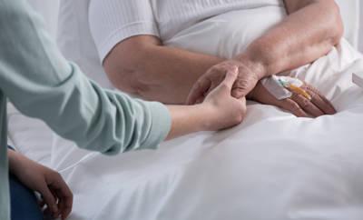 Angehöriger hält Hand eines Koma-Patienten