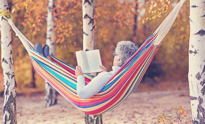 Ältere Frau, die in einer Hängematte liegt und liest.