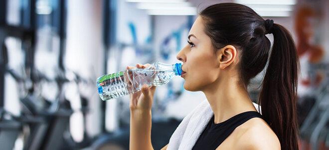 Junge Frau, die beim Sport Wasser trinkt.