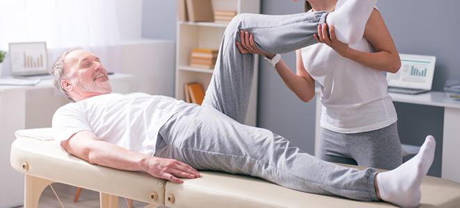 Älterer Mann bei Krankengymnastik. Er leidet an Ischialgie.