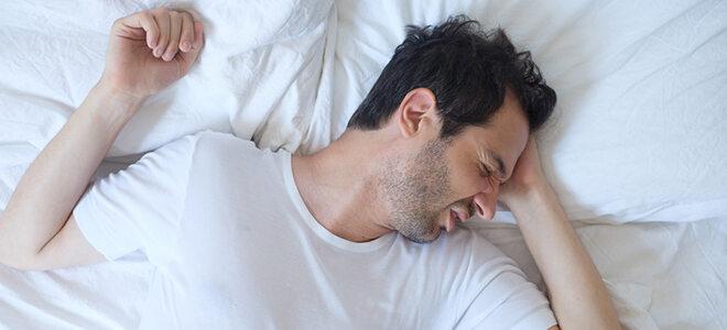 Mann, der sich im Schlaf wälzt.