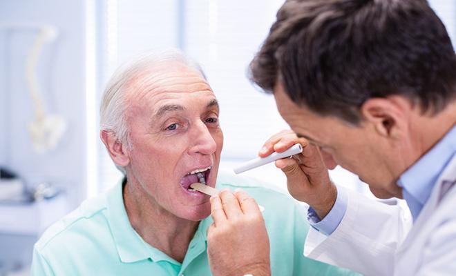 Senior, der die Zunge zum Untersuchen raus streckt.