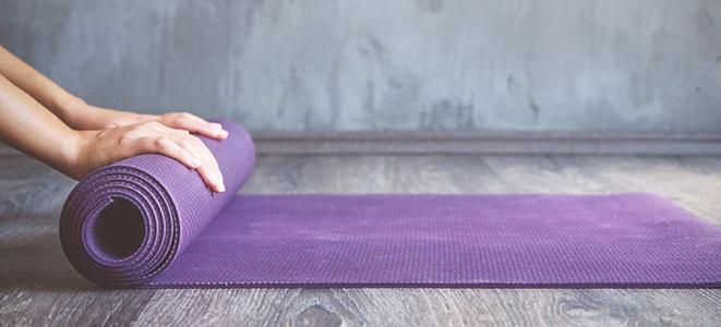Frau, die eine Yoga-Matte zusammen rollt.