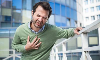 Junger Mann, der sich mit schmerzverzerrtem Gesicht an die Brust langt.