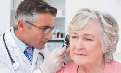 Seniorin, die am Ohr untersucht wird.