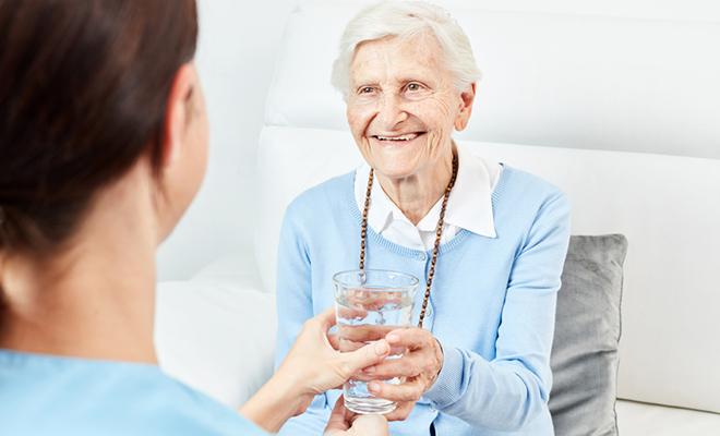 Pflegerin reicht Seniorin ein Glas Wasser.
