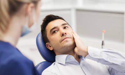 Junger Mann, der sich beim Zahnarzt an den Mund langt.