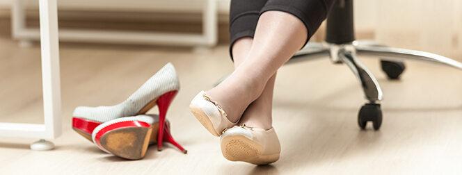 Frau, die unter ihrem Schreibtisch Ballerinas angezogen hat, High Heels liegen daneben.