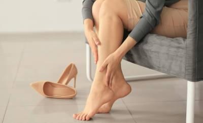 Frau, die sich die Füße reibt, daneben liegen High Heels.