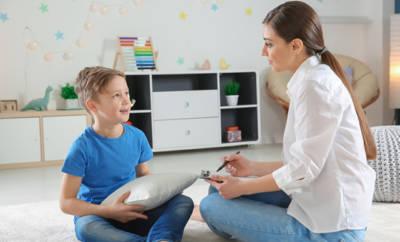 Kleiner Junge, der mit Psychologin am Boden sitzt und spricht.