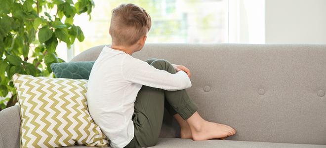 Junge, der alleine auf einem Sofa sitzt.