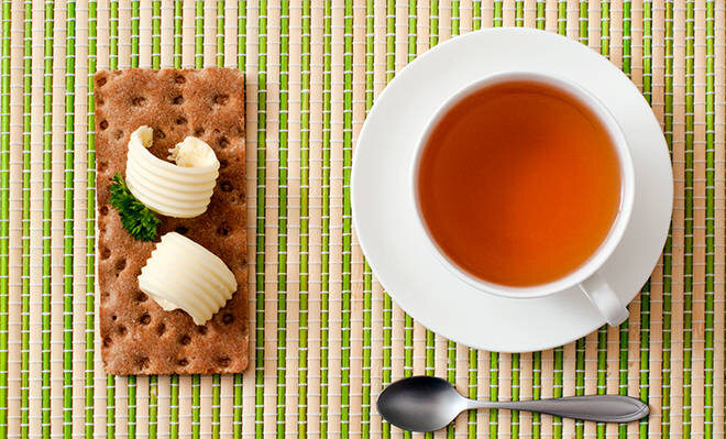 Tee und Knäckebrot auf einer Unterlage schön angerichtet.