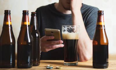 Mann, vor dem viele leere Bierflaschen stehen.