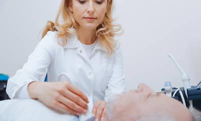Junge Ärztin untersucht Kehlkopf eines Mannes mithilfe von Ultraschall.