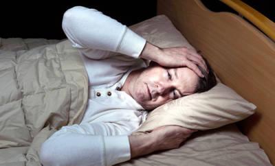 Mann der schwitzend im Bett liegt.