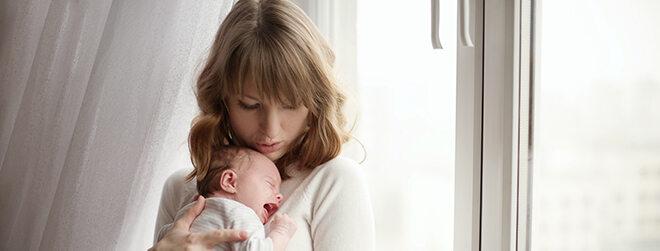 Junge Frau mit Baby auf dem Arm.