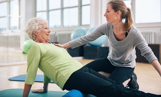 Seniorin beim Pilatestraining mit junger Trainerin.