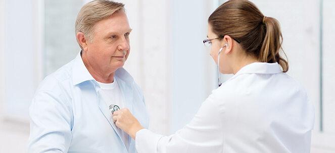 Mann, dessen Herz beim Arzt abgehört wird.