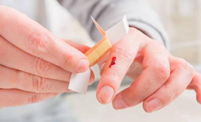 Mann, der sich Pflaster auf blutenden Finger klebt.