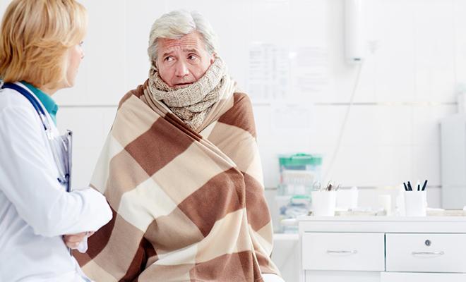 Älterer Mann mit Unterkühlung, der in deckengewickelt beim Arzt sitzt.