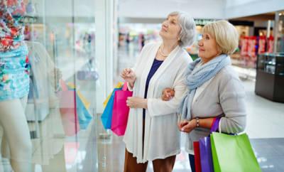 Zwei ältere Frauen, die vor Schaufenster stehen