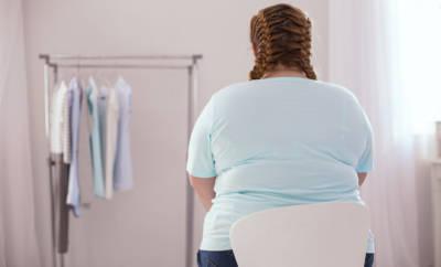 Junge, stark übergewichtige Frau, die traurig vor Kleiderständer sitzt.