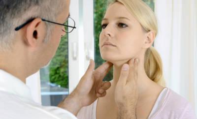 Arzt tastet die Lymphknoten einer jungen Frau ab.