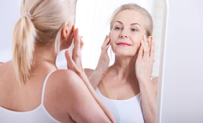 Ältere Frau, die sich kritisch im Spiegel betrachtet.