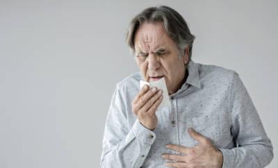 Älterer Mann, der in Taschentuch hustet.